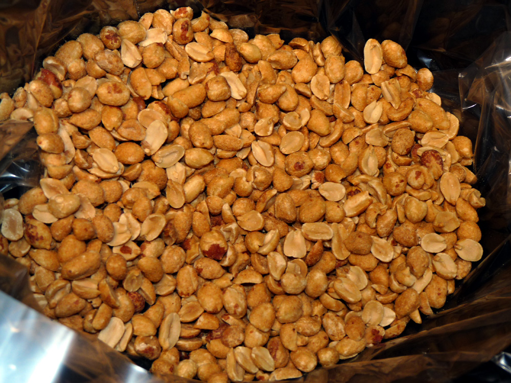 Layer half of the dry roasted peanuts in a lined crockpot