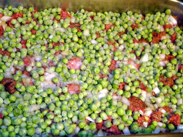 Layer frozen peas over the meat and onion.