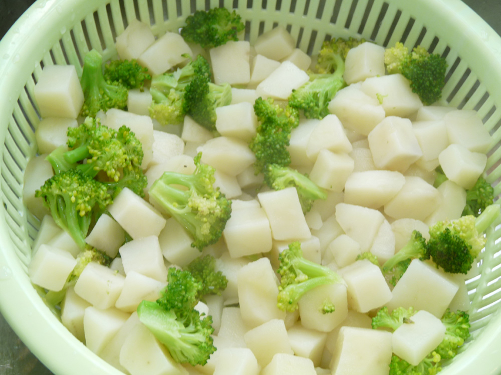 Cook potatoes for several minutes in boiling, salted water. Add broccoli and continue to cook until potatoes are fork tender. The broccoli will be firmer than the potatoes. Drain.