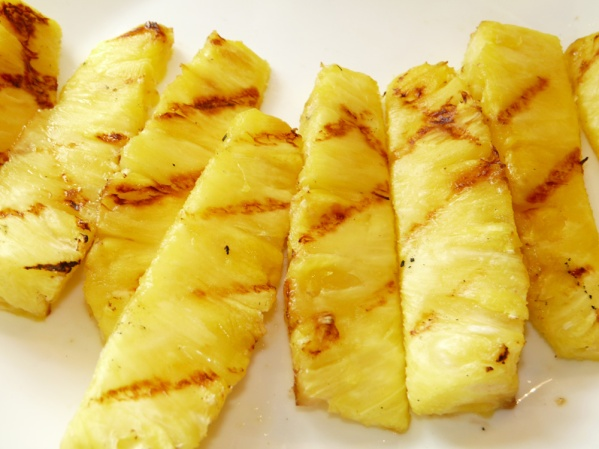 Grill pineapple slices until heated and marks appear on each side.