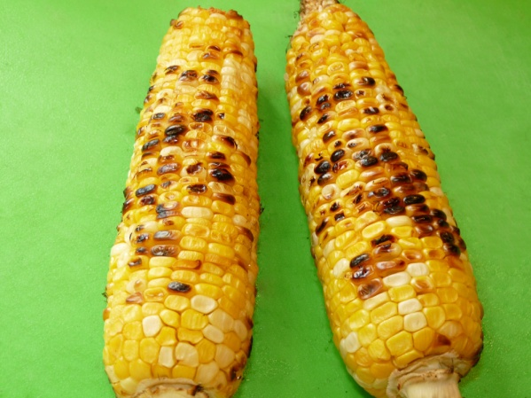 Husk corn and brush with oil. Char on grill until browned in places.