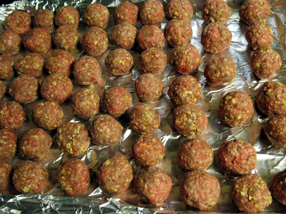 Spread stuffed meatballs on a foil-covered baking pan.