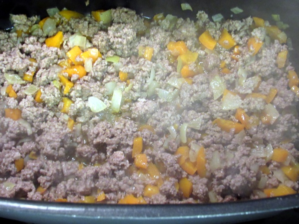When onion and pepper begins to turn translucent, add ground beet and continue to cook until beef is browned. Break the beef into small pieces as it cooks.