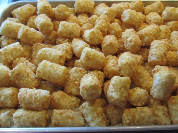 Spread tater tots as well as you can into a single layer over the top. Place in preheated oven uncovered and bake for 1 1/2 hours.