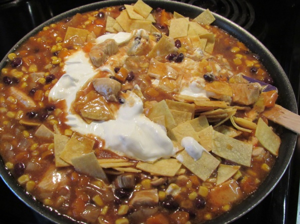 Stir in sour cream, tortilla pieces and rice. Let heat through for several minutes.