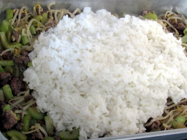 In pan layer ground beef, celery and onion, drained cans of vegetables and rice.