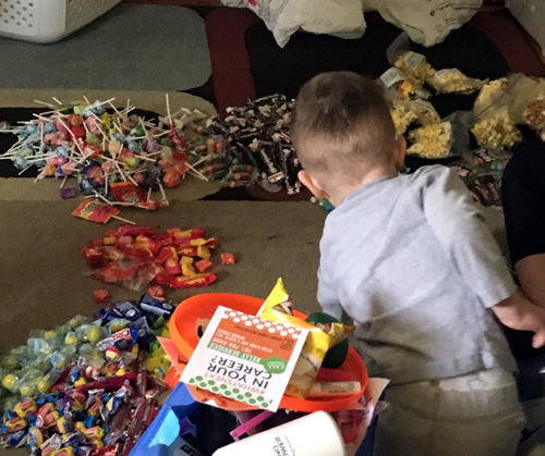 Oliver, at 2, can hardly believe the piles of candy in the living room!